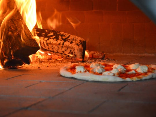 A pie bakes next to the fire at Crust & Craft.