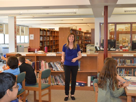 Author Wendy Mass speaks to sixth graders at Randolph Middle School during a special writer's workshop for sixth graders in the library.