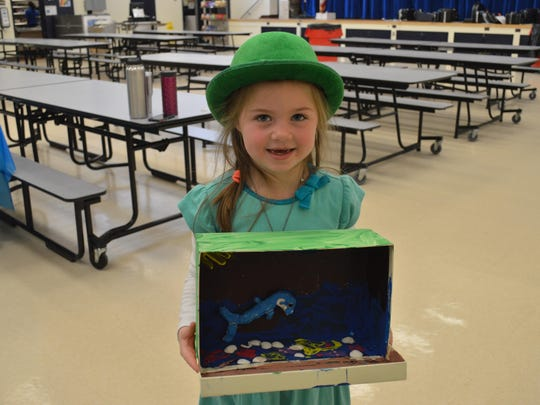 Fernbrook kindergarten student Chloe Hastings displays her project on dolphins at the Fernbrook Kindergarten Museum.