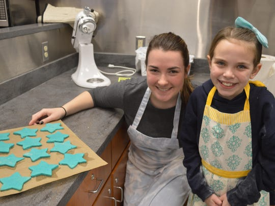 Ironia fourth grader Erin Lyons bakes cookies for the Make a Wish Foundation with Randolph High School senior Jenna Sadowski.