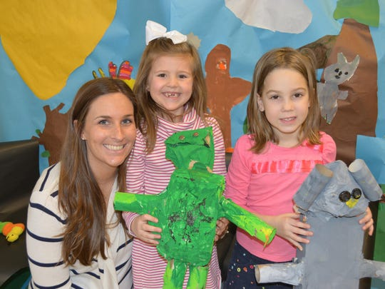 Center Grove kindergarteners in Erica Rossmann's room transformed their classroom into a zoo, decorating the walls with paintings and creating animals out of recyclables and paint. In this photo, Rossman is with Mackenzie Hutner and Kimmie Jewell and their projects.