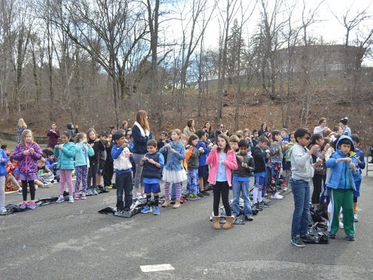 Fernbrook Elementary School students blow bubbles at an Autism Awareness Month assembly.