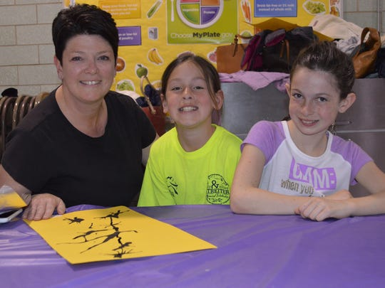 About 100 mothers and daughters spent an evening at Ironia Elementary School created a Japanese screen art project together for a Pretty in Paint night. In this photo, mom Christine Sullivan and daughters and twins Maggie and Kate Sullivan work on their project.