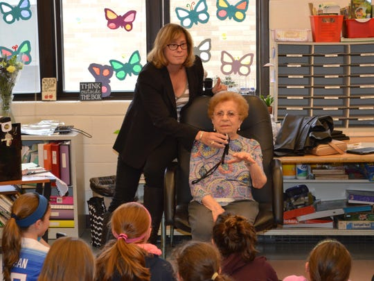 Shongum fifth grade teacher Bobbi Sobel holds the microphone for Edith Farber during her talk to fifth grades about her experience in the Holocaust.
