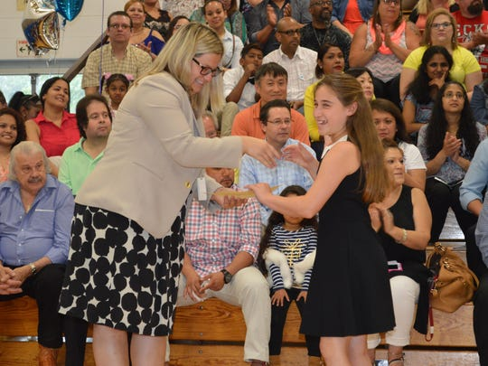 Fernbrook fifth grader Juliana Vailakis reacts as she accepts her certificate and shakes Fernbrook Principal Dr. Michelle Telischak's hand at the Fernbrook School fifth grade moving up ceremony in Randolph on June 16.