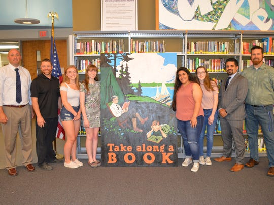 The Randolph High School chapter of the National Art Honor Society painted a new mural for the high school library. Pictured left to right, Randolph Director of Secondary Education Jonathan Olsen, Randolph High School Art Honor Society adviser Steve Coleman, Art Honor Society members Kaitlyn Kudriavetz, Emily Higgins, April Stockfish, Francesca Riggio, Supervisor of Fine and Performing Arts Frank Perrone and media specialist Steve Cullis.