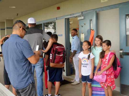 A father takes a photo of Sundale Elementary students on their first day of school just moments before entering their classroom.