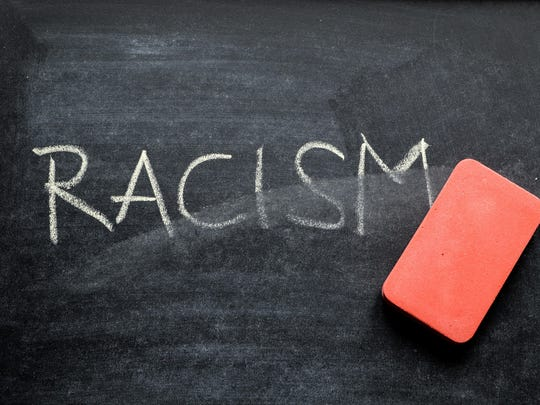 erasing racism, hand written word on blackboard being erased concept