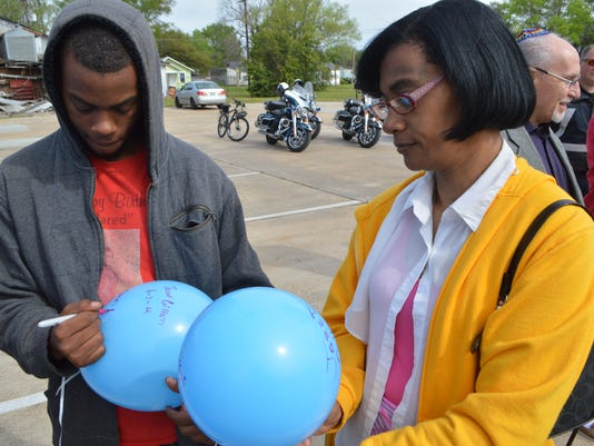 ANI Victims Rights Parade Jordan Gillam (left) and his mother Gloria Abraham write messages on balloons for the late Jared Gillam, who was slain in 2012. Both participated in the Victims Rights Parade and balloon launch held Saturday April 5, 2014 in Alexa