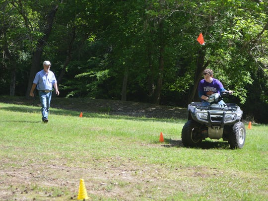 Alan Fitts, 15, drives an all-terrain vehicle around an obstacle course Wednesday as Rodney Johnson with the LSU AgCenter watches.