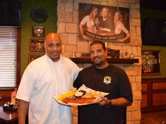 Charles Mereday, a consultant at Tilted Kilt, and Jorge Delatorre, the Tilted Kilt's kitchen manager, prepare Jimmy B's baby back ribs.