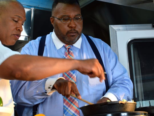 """Mayor Cedric Glover gets some culinary tips on making blackened fish and shrimp from """"Flip My Food"""" host Chef Jeff Henderson."""