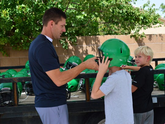 Jon Felix, left, checks the helmet his son Kurt, center, has tried on to see if it fits properly while Rylan Dalton, right, watches during the equipment handout Saturday morning for SUN Youth Football League players.