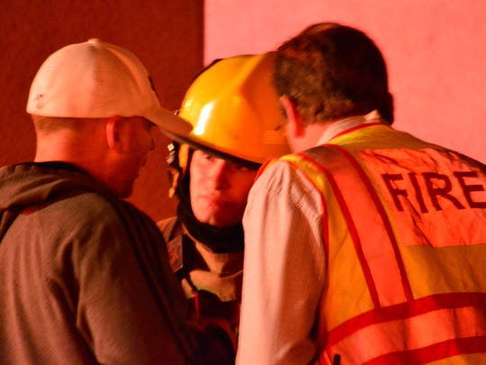 Anytime Fitness owner Roger Adams, left, talks with fire officials Thursday after his business went up in flames.