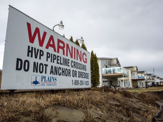 A sign warns of a petroleum pipeline owned by Plains LPG Services under the St. Clair River off of River Road in Marysville.