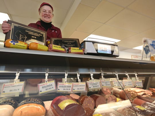 FILE - Newton Meats owner Karean VanEss Wagner poses with two 2016 Wisconsin Cured Meat Championships award plaques and the shop's sausage section.