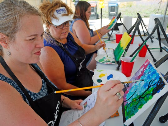Shannon Mencher of Norwalk paints her own picture at Pinot's Palette during the Des Moines Arts Festival Friday, June 24, 2016.