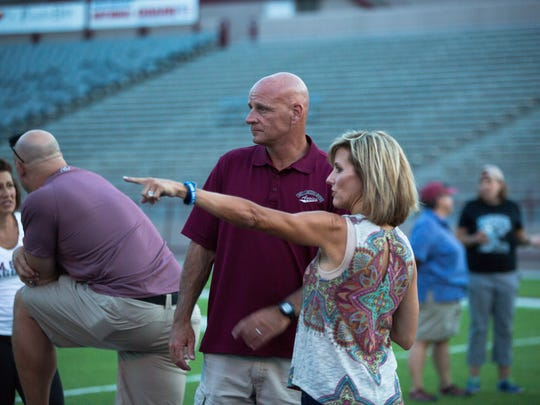 New Mexico State head football coach Doug Martin, left, and his wife, Vicki Martin watch as participants go through drills during the Aggie Women's Football Clinic on Thursday at Aggie Memorial Stadium.