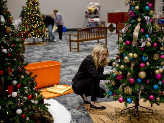 Brandi Bowman, of Midland, sets up a tree in preparation