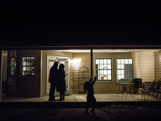 Brian and Christine Fitzpatrick walk along the porch of their new home as their daughter, Alia, 6, runs around the yard Thursday, Jan. 5, 2017 in Fort Gratiot.