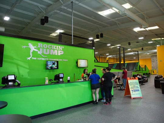Customers stand at the front desk of Rockin' Jump,