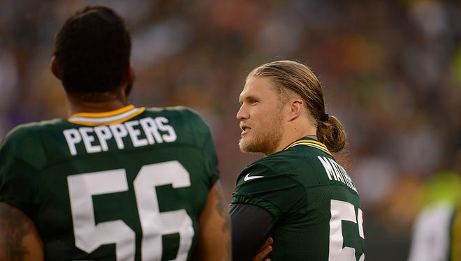 Green Bay Packers linebacker Clay Matthews visits with teammate Julius Peppers during Packers Family Night at Lambeau Field on Saturday, Aug. 8, 2015.