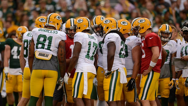 Green Bay Packers quarterback Aaron Rodgers huddles up his teammates during Packers Family Night at Lambeau Field on Saturday, Aug. 8, 2015.