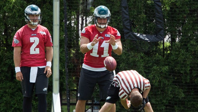 Philadelphia Eagles quarterback Tim Tebow (11) takes a snap in front of quarterback Matt Barkley (2) during minicamp at The NovaCare Complex.