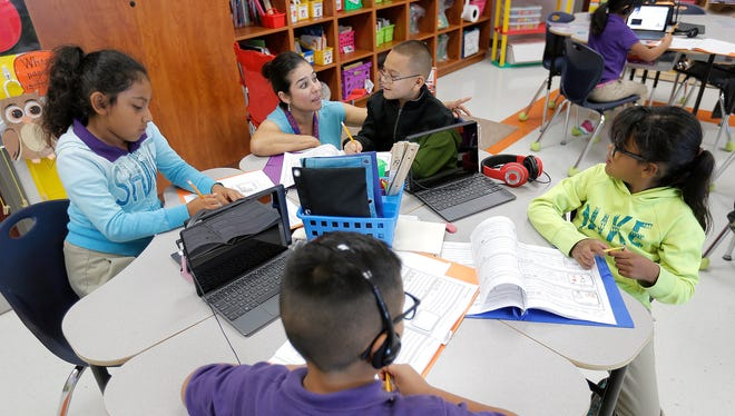 Mission Ridge Elementary School third-grade bilingual teacher Blanca Gardea works with student Jaime Torres during a writing assignment. The Socorro Independent School District uses a transitional early exit bilingual education program.