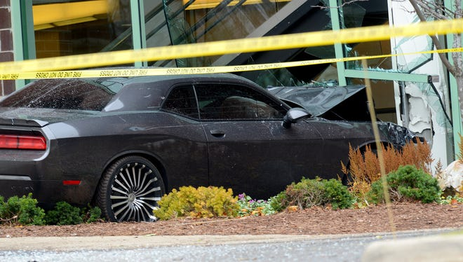 A car sits idle after ramming into the Mid-Michigan Physicians building  on Wednesday.