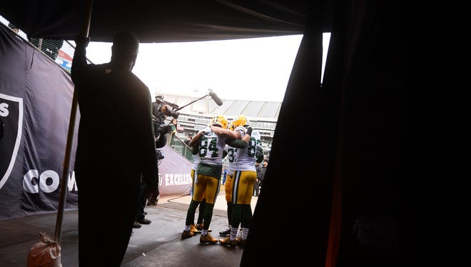 Members of the Green Bay Packers huddle up before taking the field against the Oakland Raiders at the O.co Coliseum.