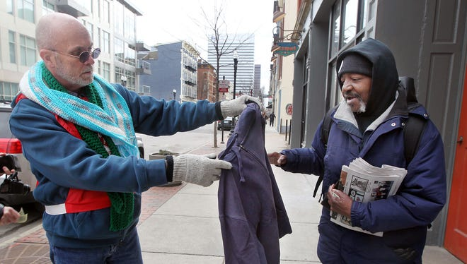 Larry Harvey (left), manager of emergency services for the Salvation Army, gives a sweatshirt to Lee McCoy.