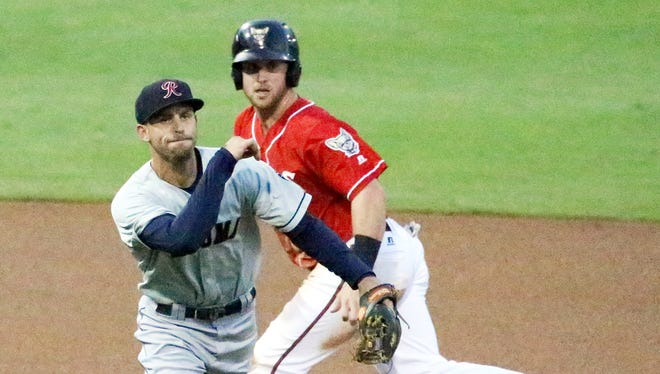 Patrick Kivlehan, right, races to third base while Tacoma third baseman Zach Shank fires to first base during Triple-A playoff action Wednesday night at Southwest University Park.