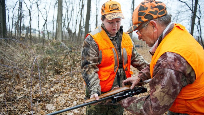 In this 2013 photo George Fuhrman, right, and his daughter Holly, 14, of York Township, prepare rifles in Shrewsbury Township. Firearms hunting season for deer opens Nov. 28.