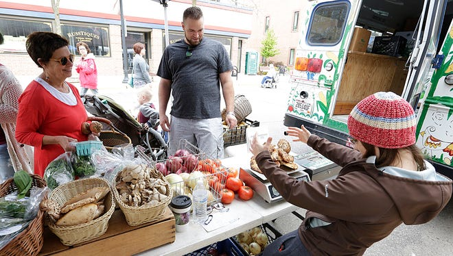 Katie Petrick (right) of Produce With a Purpose weighs some pheasant tail mushrooms for Mike Evert (center) of Fond du Lac while Mary Lou Soffa (left) of Fond du Lac waits to purchase produce Saturday May 13, 2017, during the opening weekend of the Downtown Fond du Lac Farmers Market. Doug Raflik/USA TODAY NETWORK-Wisconsin