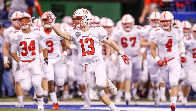The Center Grove Trojans make their way onto the field to face off against the Carmel Greyhounds in the Class 6A state title game at Lucas Oil Stadium on Friday, Nov. 25, 2016.