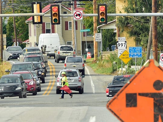Traffic backs up on Pa. 997 at U.S. 11 in Greenvillage on Wednesday afternoon as road construction continues in the area.  A flagger replaces traffic lights in the area during afternoon rush hour.