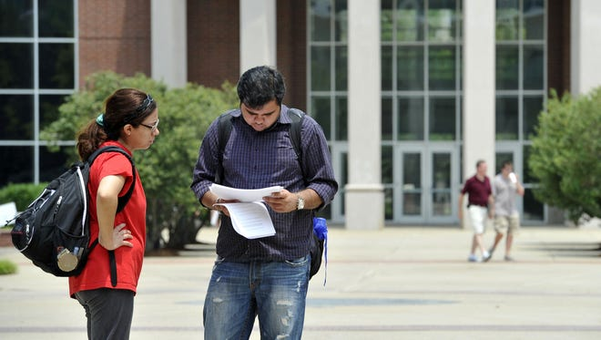 Students Silvia Guaz and Ashu Arora look over papers at MTSU on Wednesday. UT-Knoxville plans a a stricter drop policy than that at Regents schools such as MTSU. Jeanne Reasonover / The Tennessean