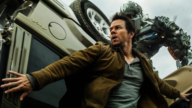 """Mark Wahlberg, front, as Cade Yeager, and Lockdown, rear, in a scene from """"Transformers: Age of Extinction."""""""