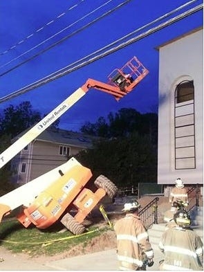 A lift is seen on its side with its bucket in the air after toppling onto its side on a slight grade at a construction site at 13 Monsey Blvd. in Monsey, May 3, 2015. The operator in the bucket was banged around and broke his wrist, Ramapo police said.