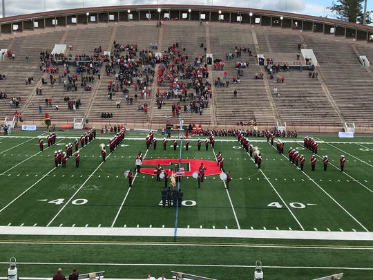 About 30 members of the Cornell University marching band take a knee along the home sideline as the remaining members of the group perform the national anthem on Saturday at Schoellkopf Field.