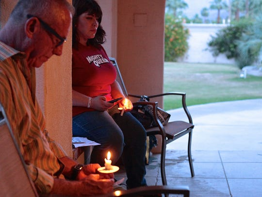 Participants hold candles in memory of transgendered lives lost. Attendee Andy Linsky and Trans Community Project organizer Shelli Orion take part in the vigil held at The Church of St. Paul in the Desert in Palm Springs on Sunday.