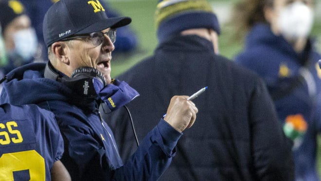 Michigan head coach Jim Harbaugh cheers on his players on the sidelines in the first quarter of an NCAA college football game against Wisconsin in Ann Arbor, Mich., Saturday, Nov. 14, 2020.