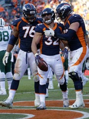 Denver Broncos fullback Andy Janovich (32) celebrates his touchdown with offensive guard Max Garcia (76) and offensive tackle Garett Bolles (72) during the second half of an NFL football game against the New York Jets, Sunday, Dec. 10, 2017, in Denver. (AP Photo/Jack Dempsey)