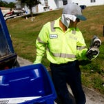 FILE: Paulino Herrera takes a shoe out of recycling bin in front of a Lehigh Acres home.