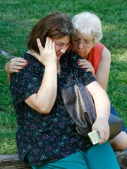 Jonell Payton, right, comforts Lisa Dew, outside the Durant home of two slain Catholic nuns  Thursday.The nuns worked as nurses at the Lexington Medical Clinic, where Dew was the office manager. Dew and a Durant police officer discovered their bodies inside the house after both nuns did not report for work. (AP Photo/Rogelio V. Solis)