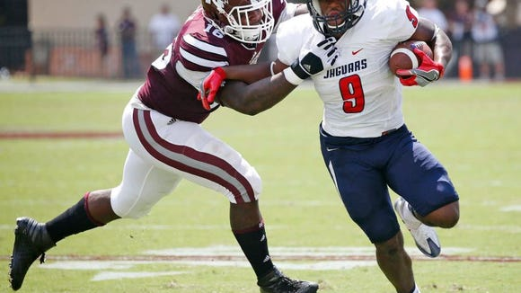 Mississippi State defensive lineman Johnathan Calvin, tries to tackle South Alabama running back Tyreis Thomas (9) in the first half of an NCAA college football game in Starkville, Miss., Saturday, Sept. 3, 2016.