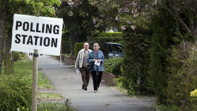 A couple walk to cast their vote at a polling station in Croydon, South London, on May 7.