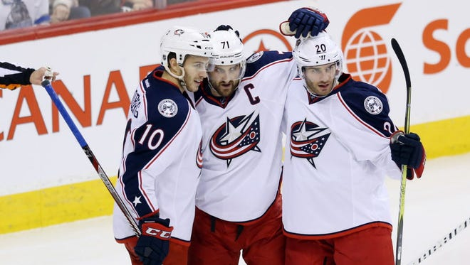 Blue Jackets center Alexander Wennberg (10) celebrates his goal against the Jets with teammates.