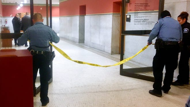 Police set up crime scene tape outside a Minneapolis police room at Minneapolis City Hall on Monday, Dec. 18. Minneapolis police say their officers have been involved in a shooting inside the department's investigative unit at City Hall.